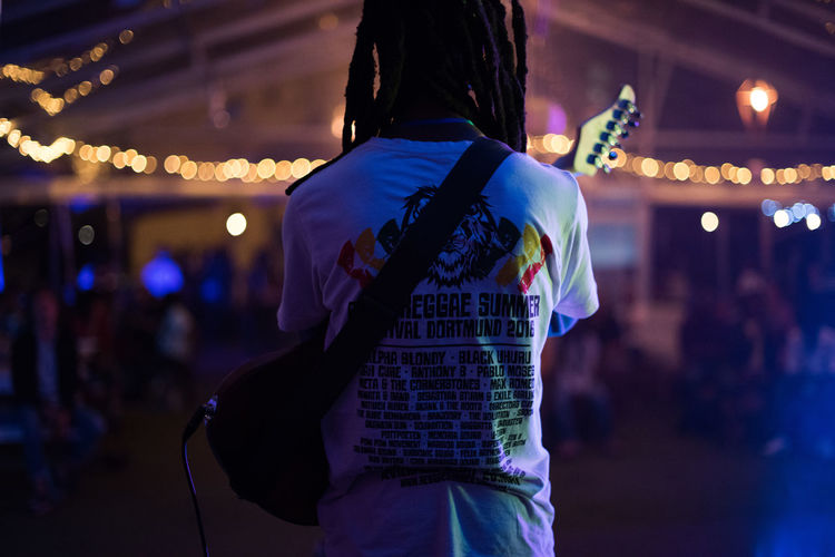 Rear View Of Man Holding Guitar Against Illuminated Lights At Night