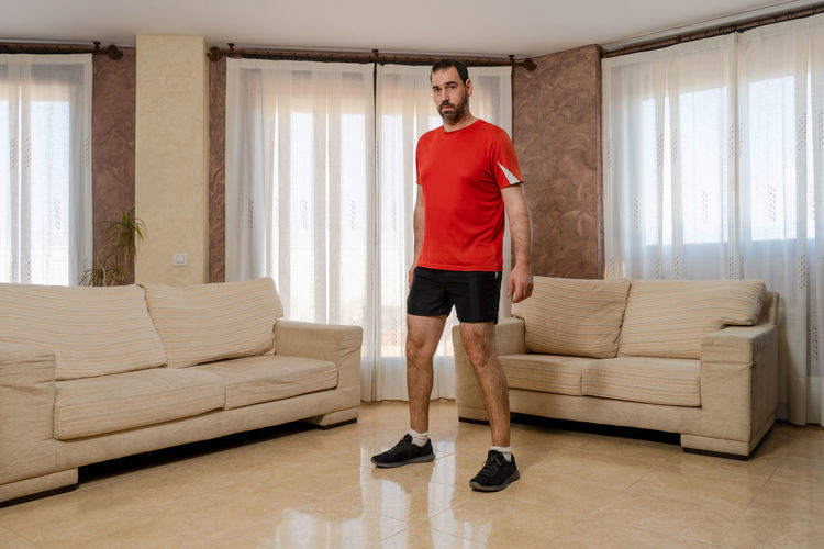 Portrait of man standing on sofa at home