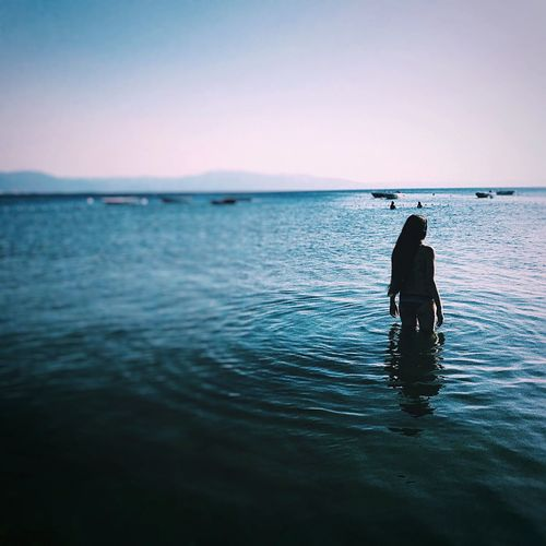 Rear view of teenage girl in sea during sunset