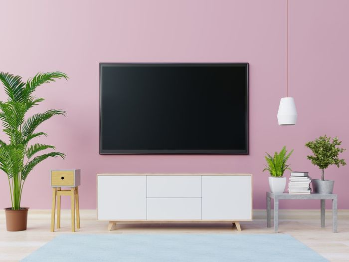 Television Set Over Cabinet Against Pink Wall At Home