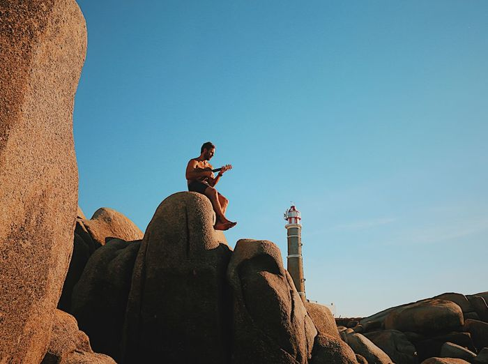 Low angle view of mid adult man playing guitar while sitting on rock formation against blue sky
