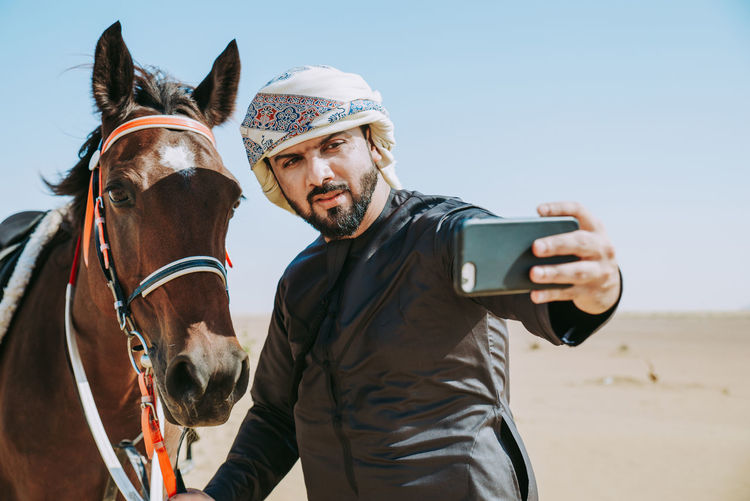 Man with traditional Kandura emirates clothes, spending time with his horse in Dubai Man Dubai Abu Dhabi Horse Desert Land Ranch People Emirates Lifestyles Animal Sheikh Kandura Traditional Headscarf United Arab Emirates Travel Flag Middle East Ethnicity Persian Gulf Emirati Muslim Riding
