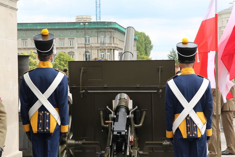 Artillerymen Standing By Cannon In City
