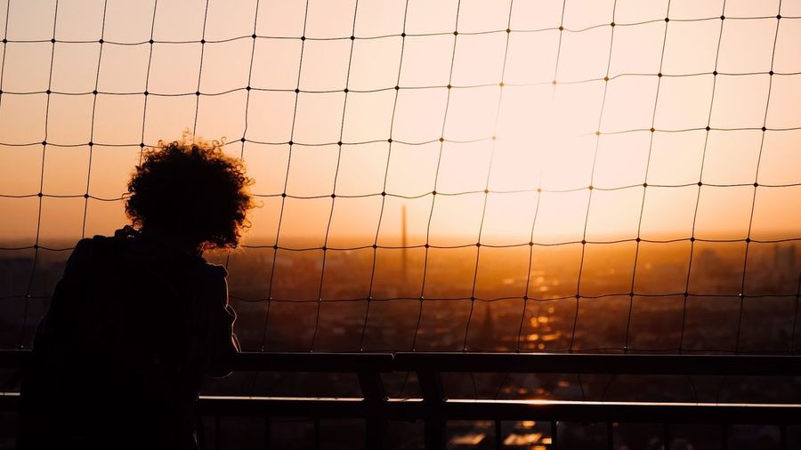 Silhouette Woman Standing By Railing With Net Against Sky During Sunset
