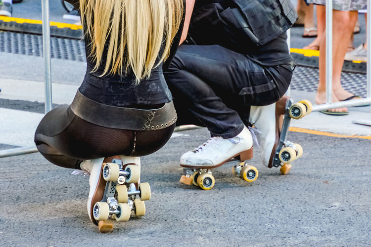 Low section of people wearing roller skates on street
