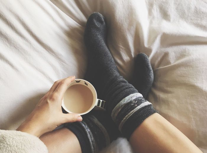 Low section of woman holding coffee cup on bed