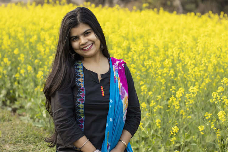 A pretty indian woman with smiling face looking at camera in mustard field