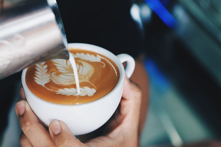 Close-Up Of Hands Pouring Milk In Coffee