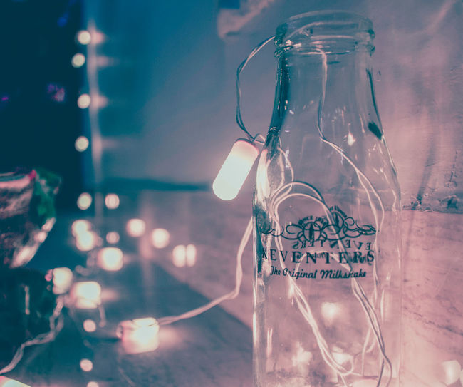 A glass bottle with light bulbs in and around. Hanging Christmas Christmas Decoration Glass Bottle Bottle Lights Bokeh Brandon Woelfel Bulbs Transparent KEVENTERs