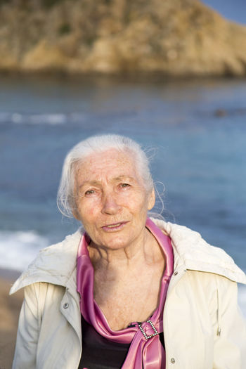 Portrait of the happy elderly woman against the sea in sunny spring day. Water Portrait One Person Adult Senior Adult Looking At Camera Focus On Foreground Front View Real People Day Leisure Activity Women Lifestyles Sea Nature Smiling Outdoors Warm Clothing Scarf Hairstyle White Hair Elderly Happy Aged Senior Women My Best Photo