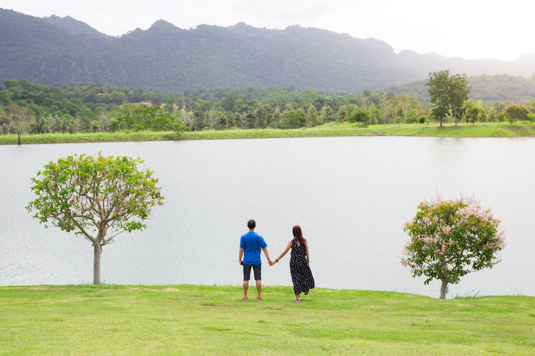 Behind of couple holding hand with full nature grass field , lake , mountain and tree . Romance seen Beauty In Nature Bonding Couple - Relationship Day Full Length Grass Lake Leisure Activity Love Men Nature Outdoors Plant Positive Emotion Real People Scenics - Nature Standing Togetherness Tranquility Tree Two People Women