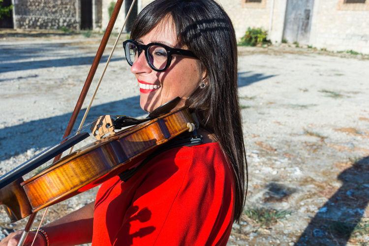 Woman playing violin outdoors