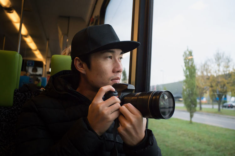 Close-up of man photographing while sitting in train