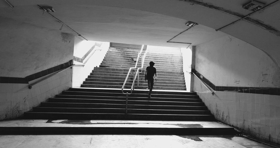 Rear view of man walking on stairs