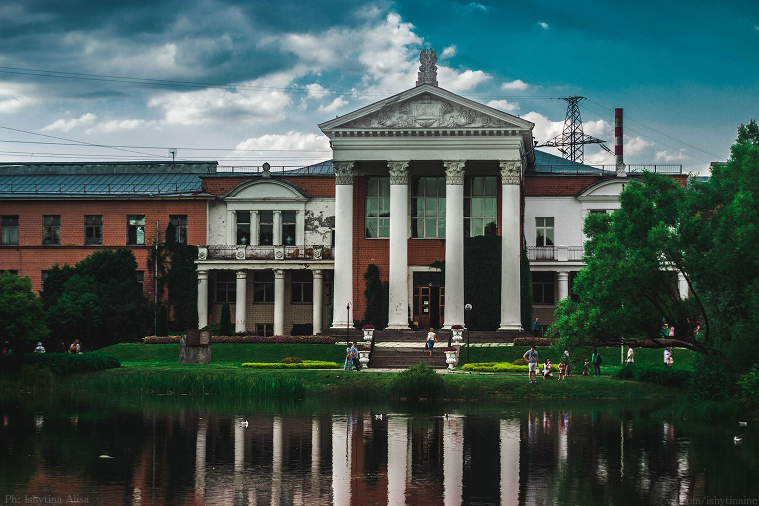 architecture, building exterior, built structure, water, sky, reflection, waterfront, cloud - sky, fountain, pond, cloud, tree, facade, lake, outdoors, river, building, cloudy, no people, day