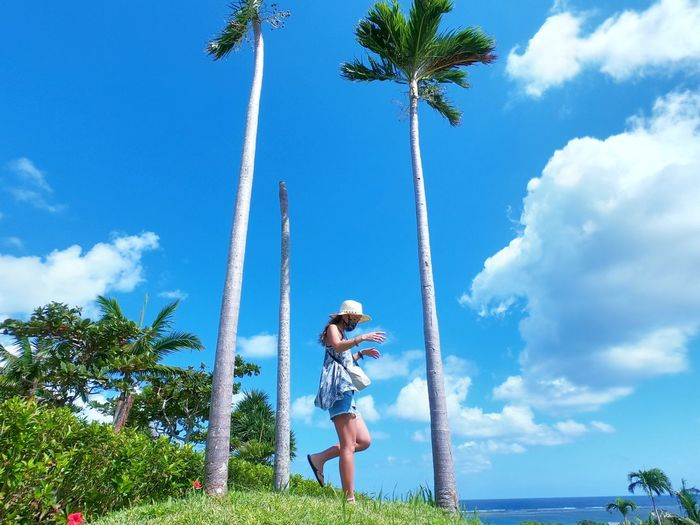 Woman standing by palm trees against blue sky