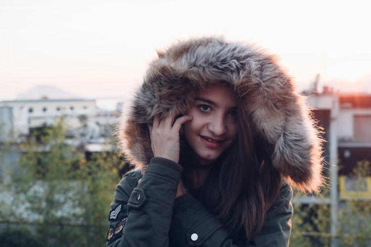 Portrait of young woman wearing fur coat against buildings