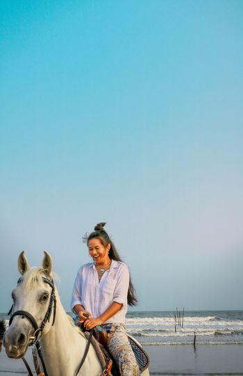 Woman riding horse in sea against clear sky