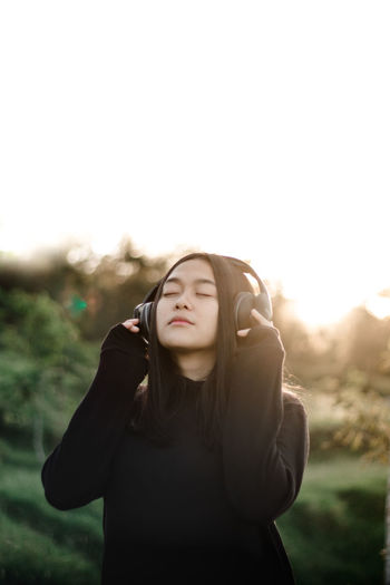 Woman listening music against clear sky