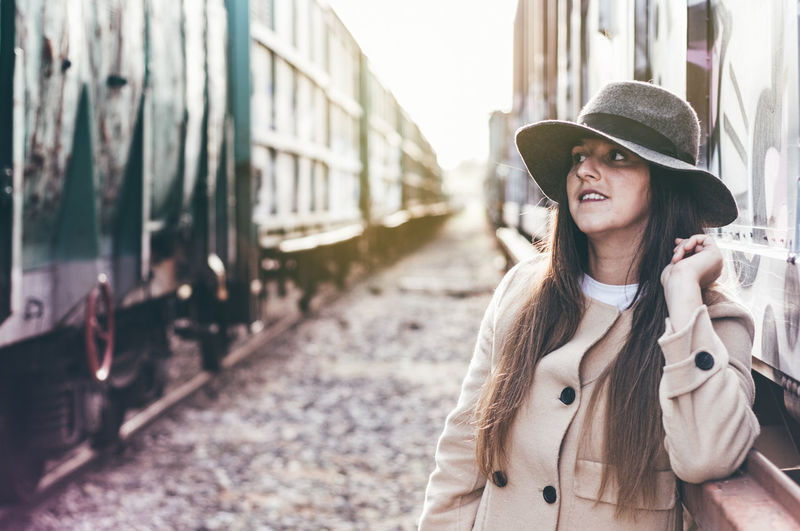 Portrait of a woman with hat and beige jacket leaning between two abandoned train cars.