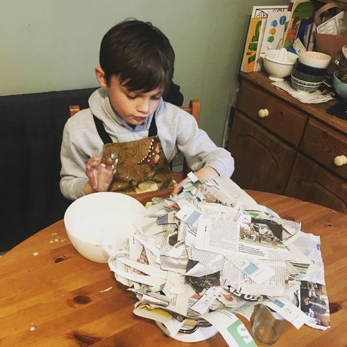 Paper machè Indoors  One Person Childhood Real People Sitting Lifestyles Day People Art Creative Homework Newspapers Recycling Paper Mache Kitchen Table