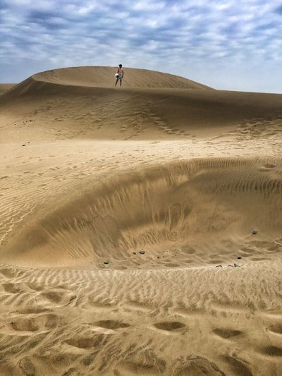 Distant view of man standing on sand dunes at desert