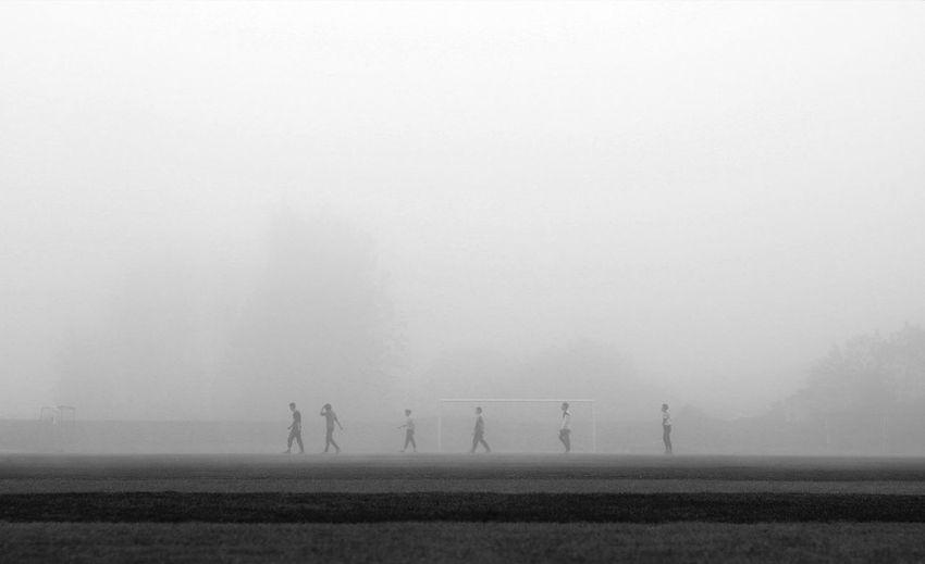 Male friends walking on soccer field during foggy weather