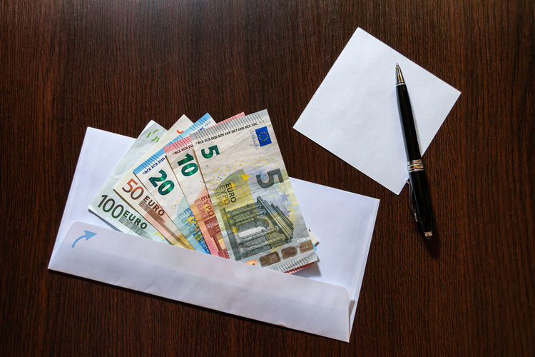 White envelope with Euro bills over wooden background Bribe HUNDRED Loan  Bills Bribery Close-up Corruption Currency Envelope Euro Fifty Finance Five High Angle View Indoors  No People Paper Currency Pen Pencil Table Ten Twenty Wealth White Wooden