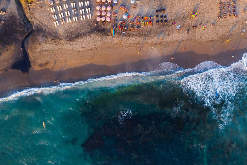 Aerial view of people enjoying on beach against sea