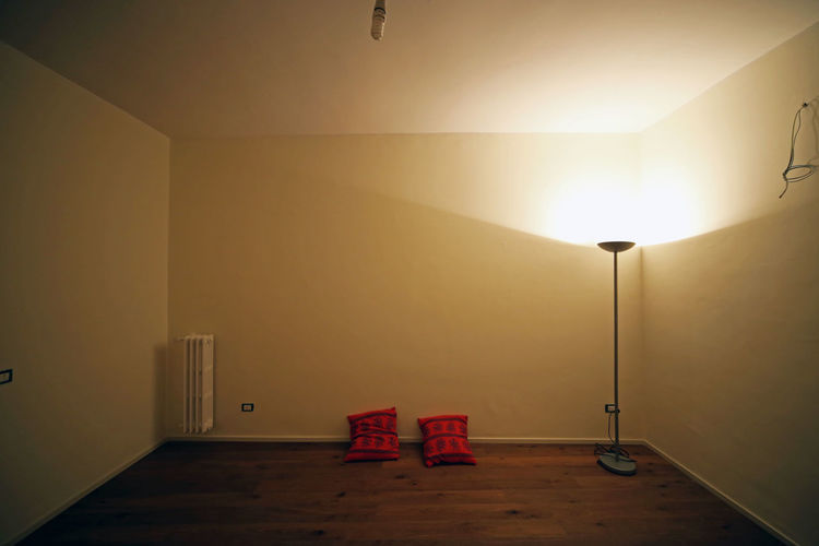 Empty Room With Cushions And Illuminated Lamp
