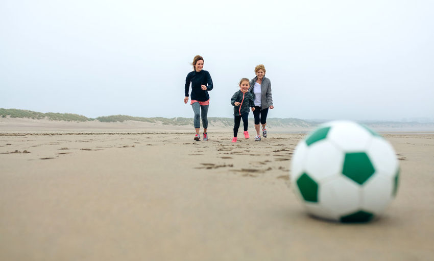 Happy Family Playing With Ball At Beach