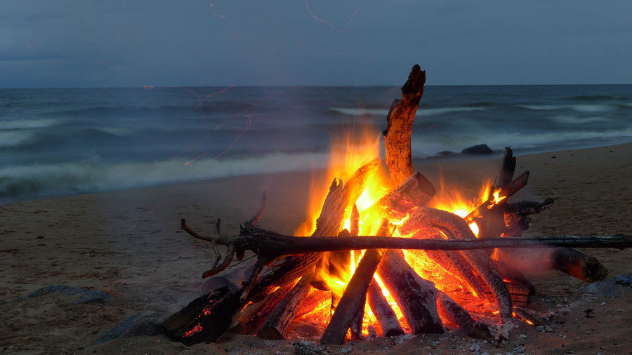 Bonfire on wooden structure in sea against sky