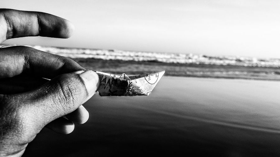 Cropped hand of person holding paper boat by lake