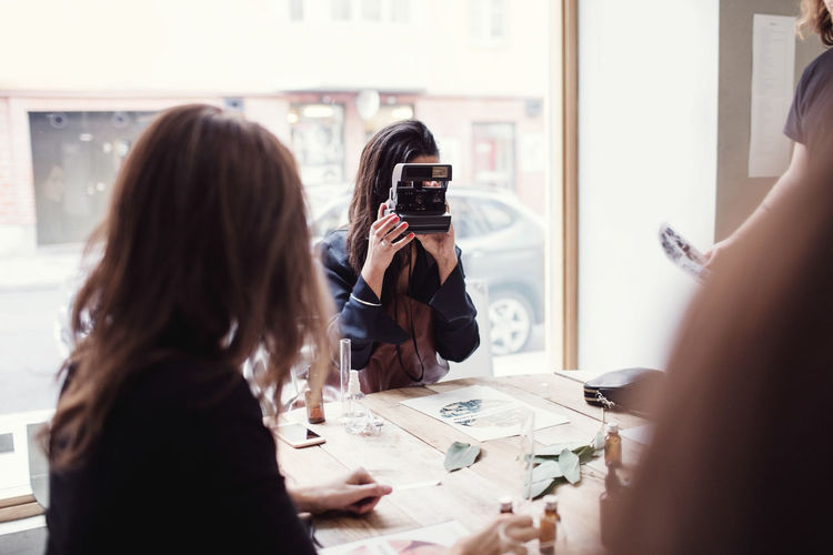 Rear view of woman photographing with camera on table