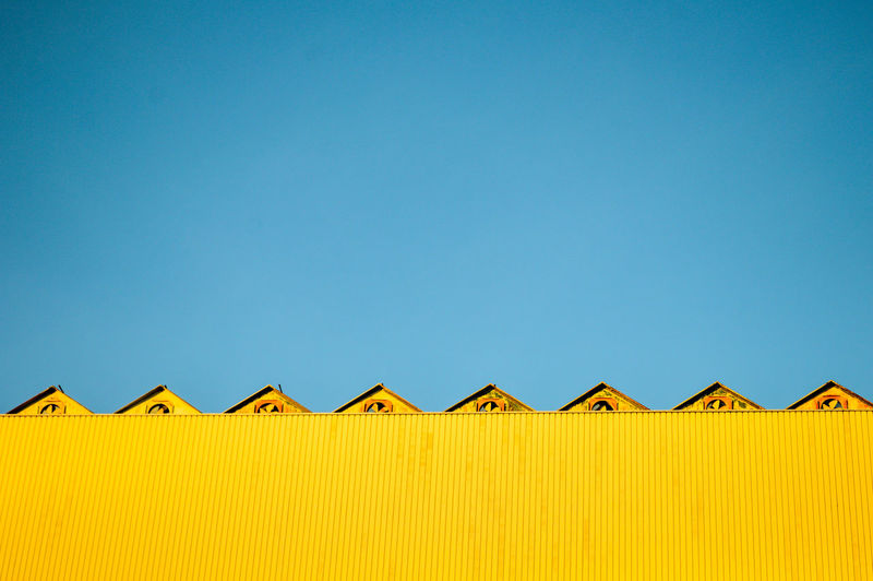 Low angle view of yellow built structure against clear blue sky