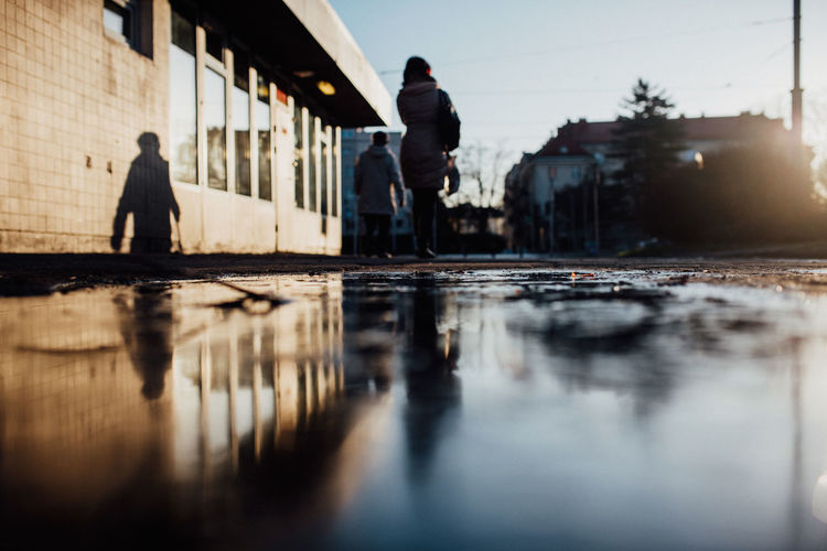 Rear view of people walking on puddle on footpath in city against sky