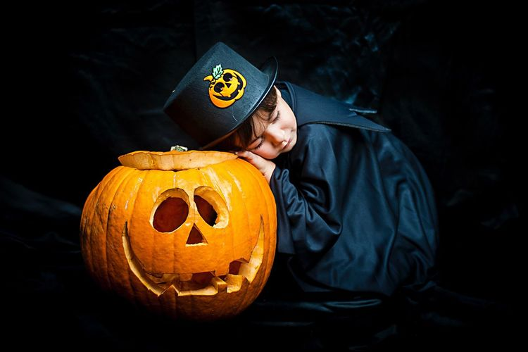 Boy in costume leaning on pumpkin against black background