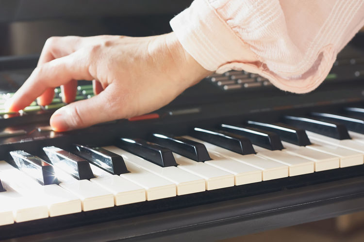 Female musician playing the digital piano or electronic keyboard at home. music education online.