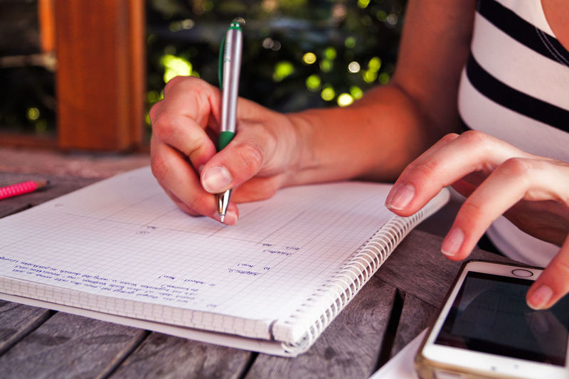 Midsection of woman studying while using smartphone on table