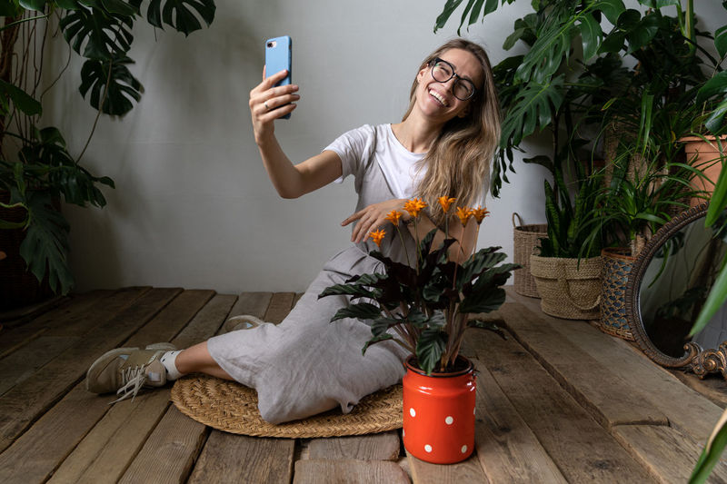Young woman using mobile phone while sitting on floor