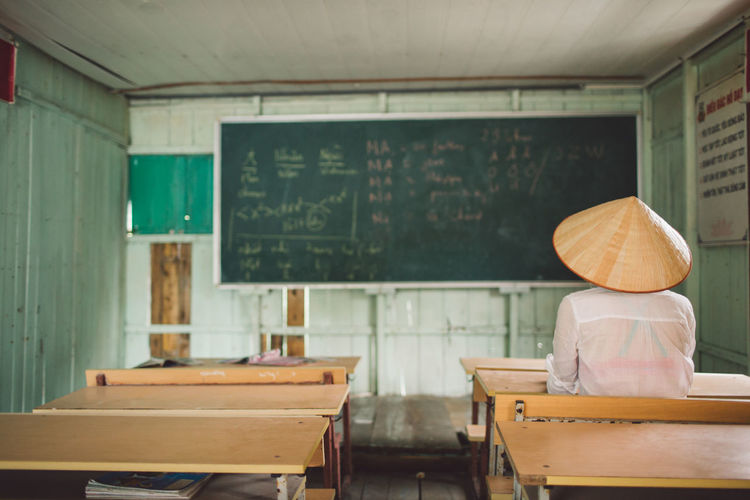 Rear view of person sitting in classroom