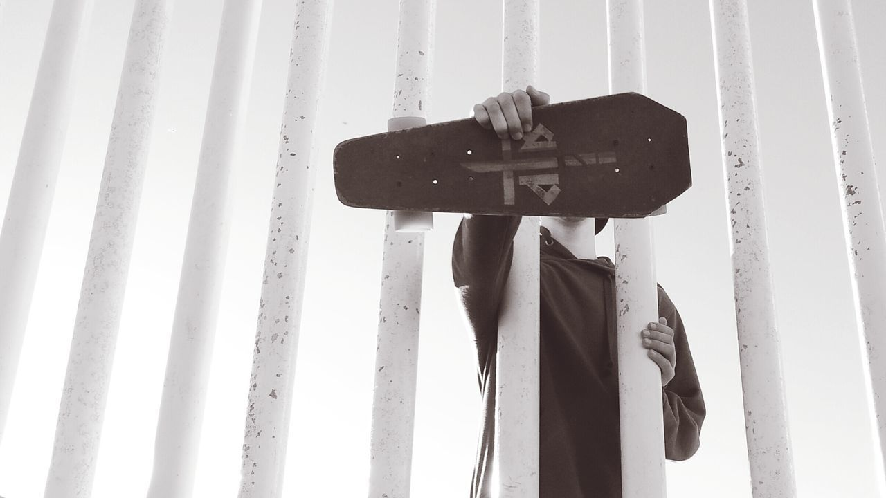 Man Holding Skateboard While Standing By Fence