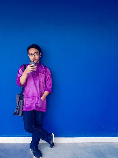 Portrait of young man wearing eyeglasses standing against blue wall