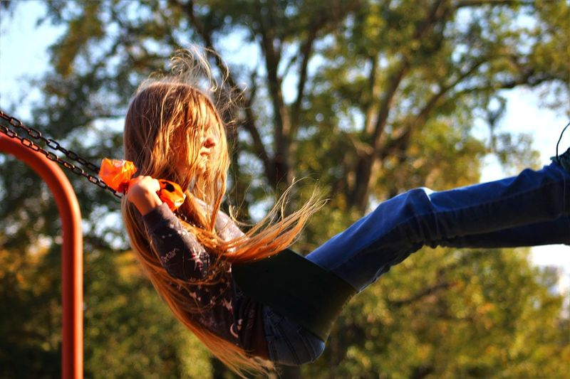Side view of girl swinging at playground
