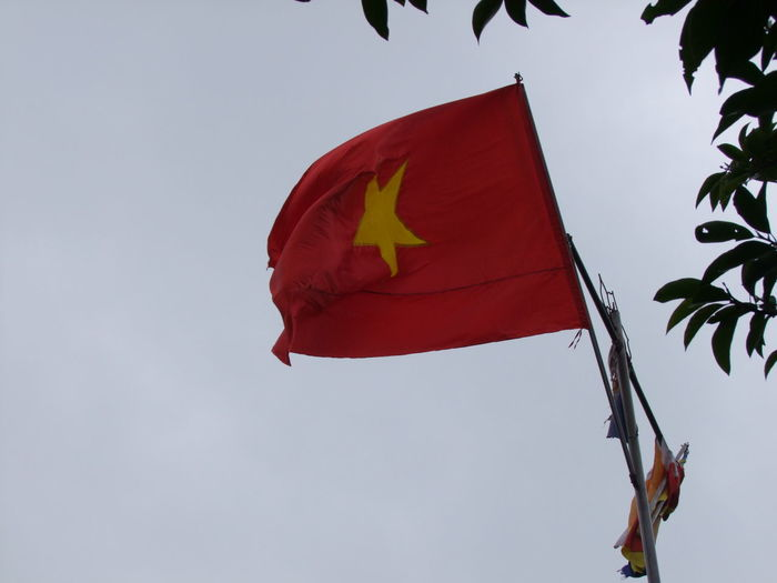 Low angle view of vietnamese flag against sky