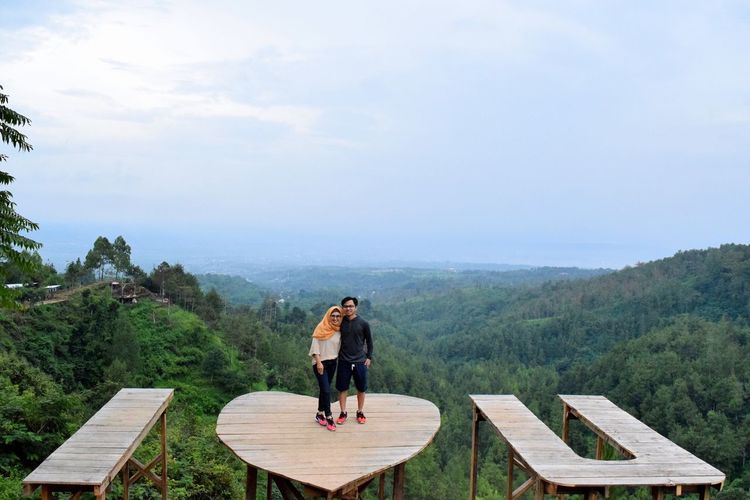 Couple standing on heart shape table against sky