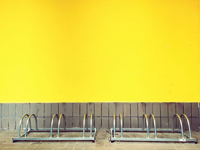 Wall Building Building Exterior Color Yellow bicycle stands racks Bike Stand plaster Paint metal stark contrast horizontal Parallel Lines Empty Places Empty Space Background Textures And Surfaces Still Life Stillness Waiting leaving gone away Farewell 2 things 6 Possibilities