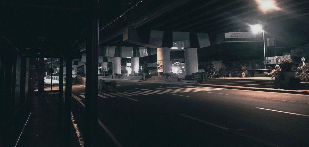 Road by illuminated city at night