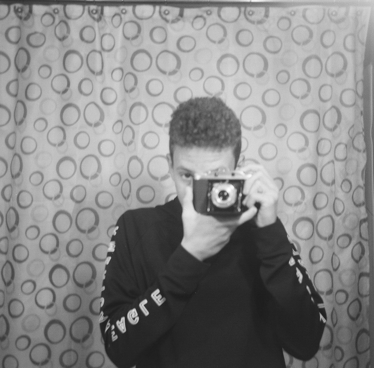 one person, photography themes, portrait, looking at camera, hiding, holding, indoors, front view, camera - photographic equipment, young adult, photographer, spy, one man only, standing, headshot, photographing, technology, men, well-dressed, adult, adults only, only men, people, day