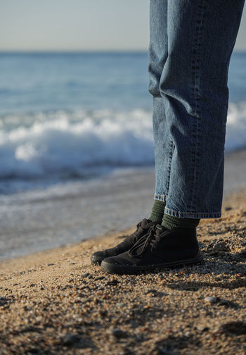 Low section of person standing on beach